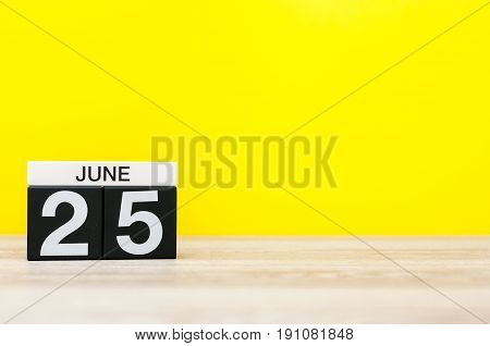 June 25th. Day 25 of month, calendar on yellow background. Summer day. Empty space for text.