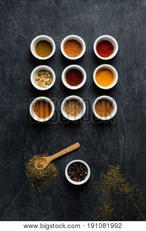 Overhead flatlay shot of a variety of spices in white bowls with scattered herbs and wooden spoon on dusty blackboard.