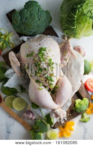 A whole uncokoked chicken with vegetables on a wooden chopping board
