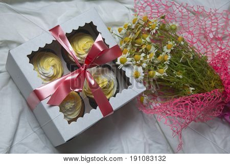delivery box with delicious freshly baked homemade lemon muffins cupcakes with butter cream for present with bouquet of chamomile flowers copy space