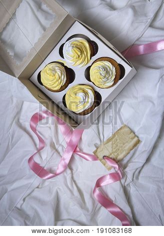 delivery box with delicious freshly baked homemade lemon muffins cupcakes with butter cream for present copy space