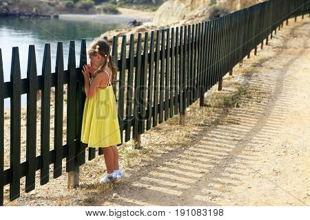 Little girl looks at the sea through a fence