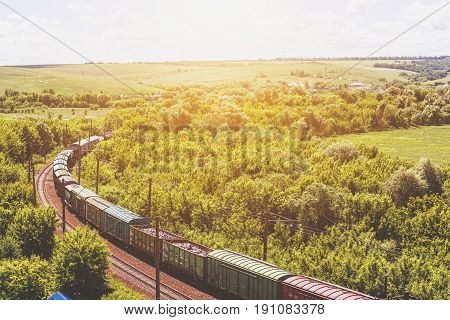 Freight train rides through a beautiful natural summer landscape flooded with sunlight, railroad track, train transportation concept