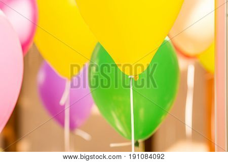 Helium multicolored balloons with ribbons hanging at ceiling