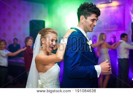 Bride Smiles While Dancing With A Groom Holding His Back From Behind
