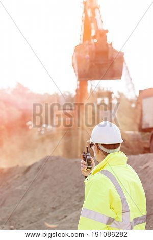 Side view of engineer using walkie-talkie at construction site poster