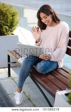 Instant connection. Excited adorable genuine woman making a video call while using modern technologies for communicating with people from all around the world
