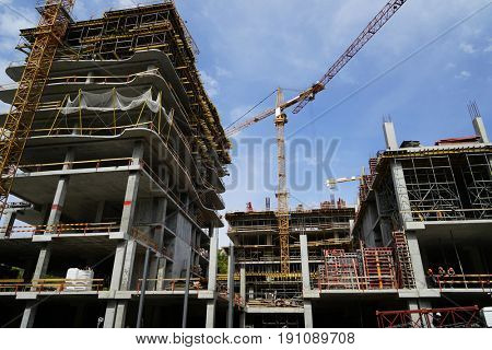 Construction crane and unfinished buildings with blue sky on background