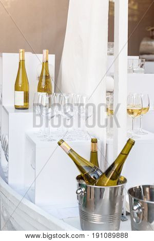 Bottles of white wine standing on serving table. Outdoor party, catering service