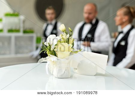Blurred background, professional waiters standing in a row. Outdoor party with finger food. Catering service