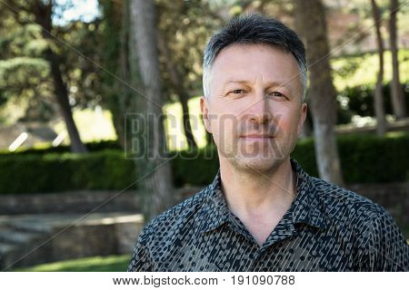 Outdoor male portrait. Mid adult man looking at camera over spring park outdoor