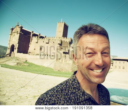 Happy smiling man over ancient spanish castle Javier, Navarre, Spain. Cultural and historical spanish heritage, architectural sight, wide angle, image toned