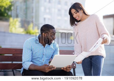 Fresh data. Ambitious inspiring open girl demonstrating the resent sales report to her friend who working outside and using his laptop