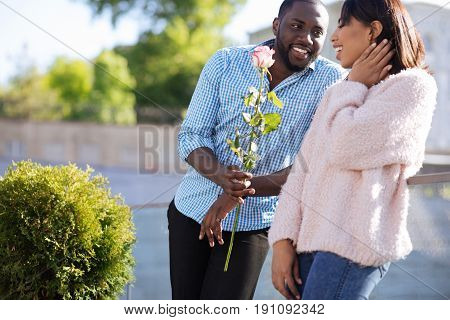Beauty for beauty. Young polite charming man asking a girl out on a date and showing up holding nice flower in his hands