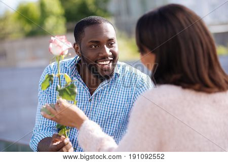 For you, my love. Enthusiastic handsome pleasant guy making his girlfriend smile while surprising her with little gift during their causal date