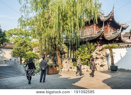 Shanghai, China - Nov 4, 2016: In Yu Yuan (Yu Garden) - A tranquil traditional Chinese architectural scene, featuring landscaped trees, rockery, and building. Visitors in the foreground.