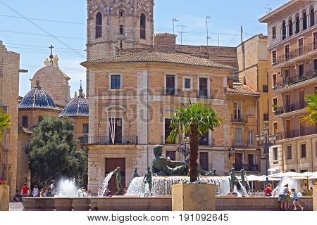 Hot summer day on the streets of Valencia Spain. Plaza Virgen in the city center of Valencia with a fabulous fountain.