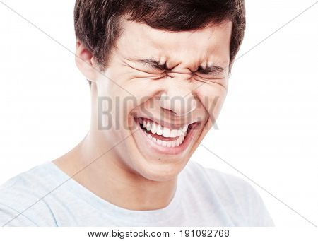 Face close up of young hispanic man laughing out loud with closed eyes - laughter is best medicine concept
