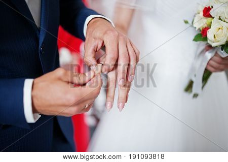 Amazing Couple Putting Wedding Rings On Fingers Of Each Other. Close Up Photo