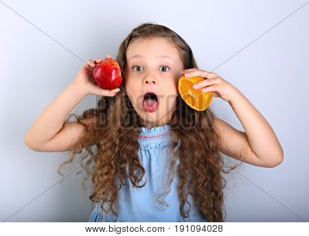 Joying Humor Grimacing Happy Kid Girl With Curly Hair Style Holding Citrus Orange Fruit And Red Appl