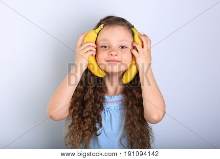 Playful Happy Fun Long Hair Kid Girl Holding Yellow Bright Bananas Near The Face On Blue Background