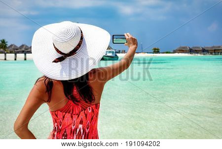 Woman with white hat takes a photo of a Maldivian beach setting