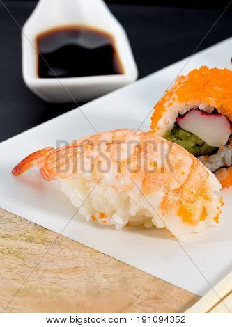 nigiri piece on marble presentation table with soy sauce