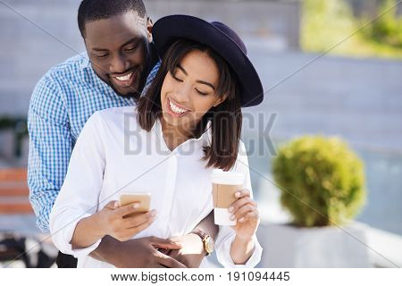 What are you doing. Young affectionate romantic guy having a date and sharing an intimate moment as his girlfriend taking a moment for checking her mail