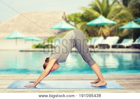 fitness, sport, people and healthy lifestyle concept - woman making yoga in downward facing dog pose on mat over beach and swimming pool background