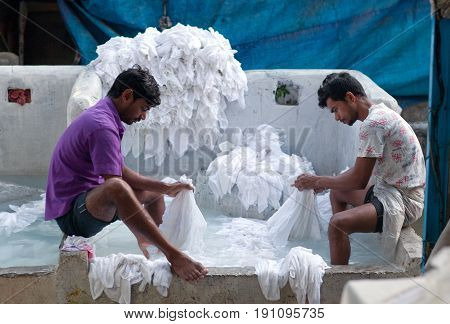 MUMBAI, INDIA - JANUARY 12, 2016: Indian workers washing clothes at Dhobi Ghat, a well know open air laundromat in downtown of Mumbai in Maharashtra State