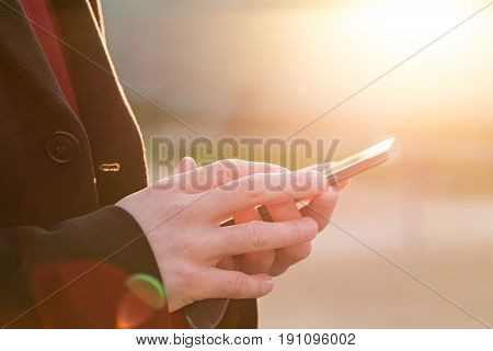 Man using his Mobile Phone outdoor close up
