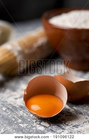 closeup of a cracked egg, an earthenware bowl with flour and a wooden rolling pin on a rustic table sprinkled with flour