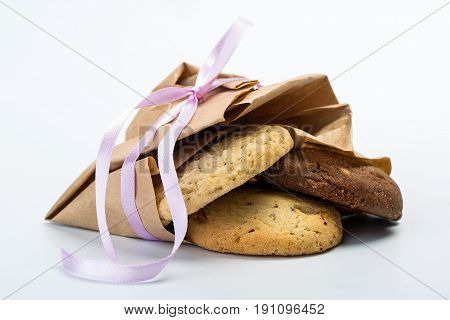 Pile of homemade cookies isolated on white background. Cookies wrapped in a paper on the table.