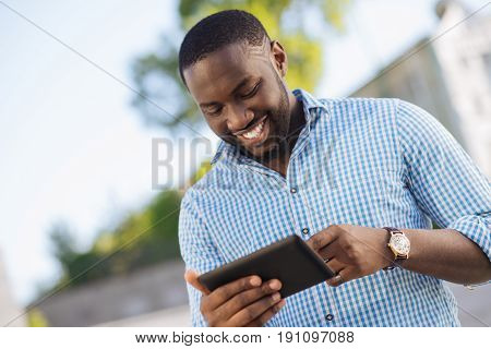 Time for entertainment. Easygoing witty joyful guy using his smartphone for chatting with his friend and reading latest news