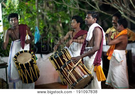 KERALA, INDIA - JANUARY 15, 2016: Indian drummers playing Chenda drums during Theyyam ceremony.