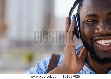 Active listener. Dynamic cheerful classy guy taking a walk around the city and wearing headphones for listening to his perfect playlist