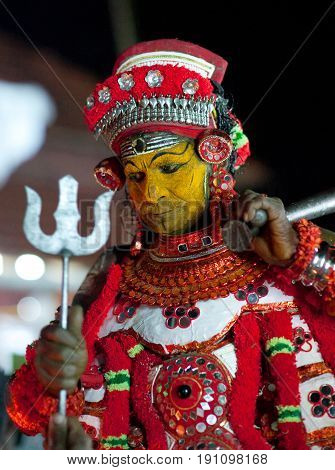 KANNUR, INDIA - JANUARY 15, 2016: Indian man conducts Theyyam ceremony. Theyyam is a ritualistic folk art form of North Malabar in Kerala.
