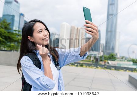Woman taking selfie with mobile phone with love finger gesture in Hong Kong