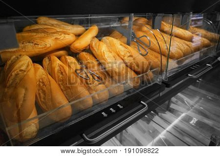 Show-case with delicious fresh bread in bakery