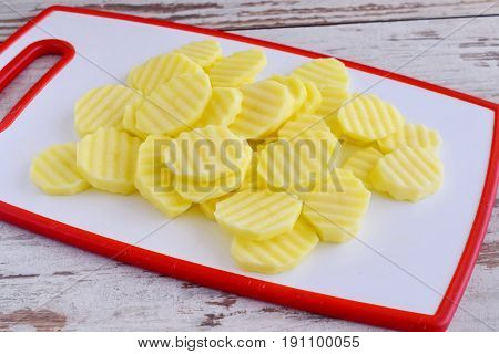 Potato cut in clices with a rib knife on a white cutting board. Step by step cooking