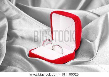 Wedding rings in red box on textile background