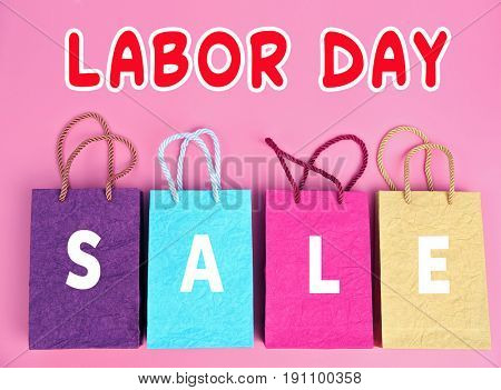 Concept of LABOUR DAY SALE. Shopping bags on color background