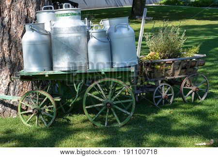 Several old milk churns on a wagon at the