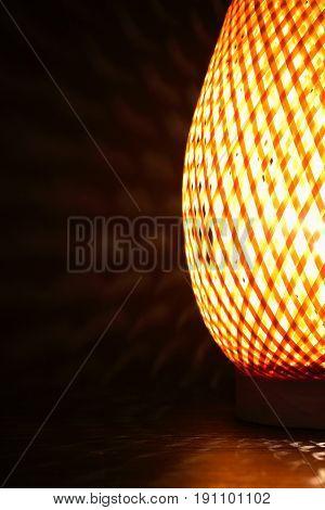 Nice wicker glowing desk lamp closeup on dark background