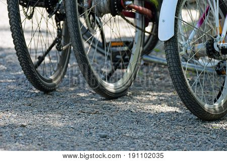 Three bicycles parked outside. Close up of rear wheels.