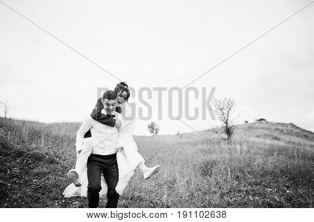 Happy Bride Riding Her Husband's Back On Their Wedding Day On The Of Hill With Tall Grass.