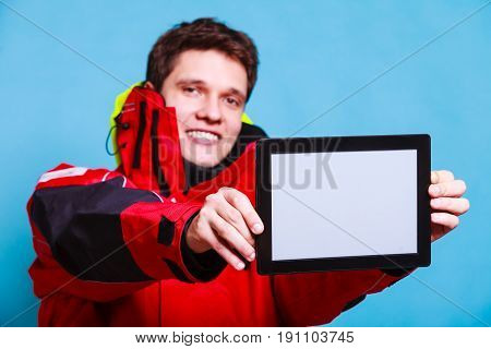 Young male with tablet. Man in waterproof clothes holding device. Adventure danger technology internet concept.