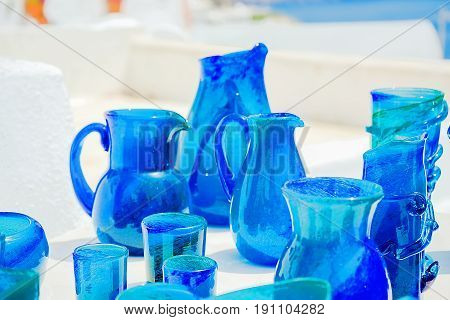 Blue glassware on a background of white stucco walls of the island of Santorini Greece. Selective focus