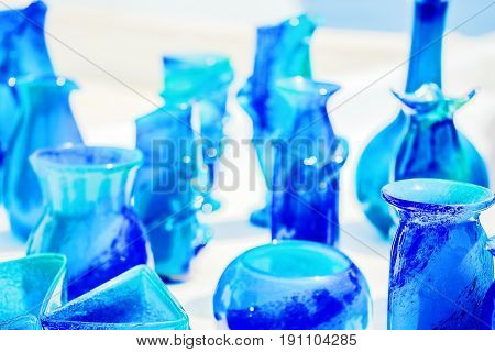 Blue glassware on a background of white stucco walls of the island of Santorini Greece. Background blurred selective focus