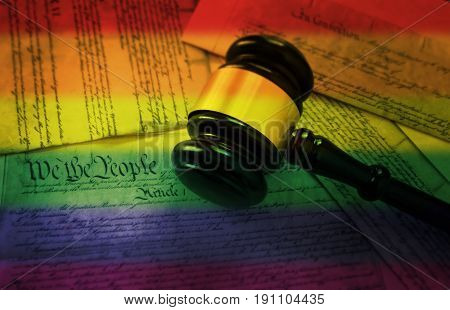 Court gavel on rainbow flag colored pages of the United States Constitution -- gay rights concept